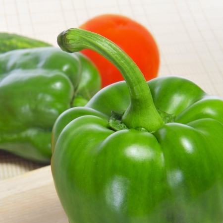 bell peppers: closeup of some green bell peppers and a tomato on a kitchen worktop