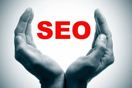 man hands forming a cup and the word SEO, search engine optimization, written in red photo