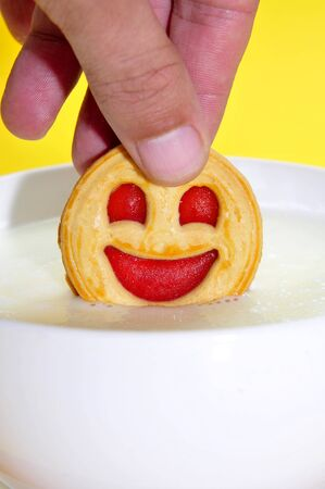 breakfast smiley face: someone soaking a smiley face biscuit in a bowl with milk