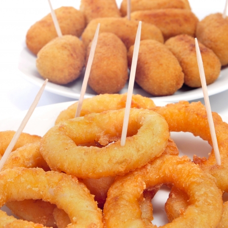 some plates with spanish calamares a la romana, squid rings breaded and fried, and croquettes served as tapas photo