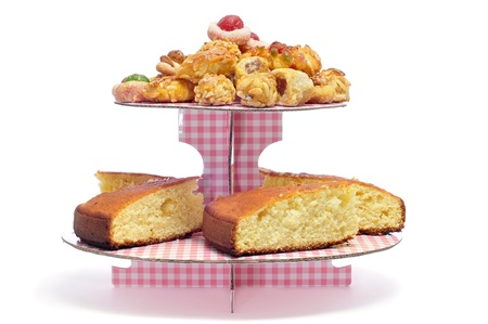 sponge: some pastires, as panellets, typical pastries of Catalonia, and sponge cake displayed in a cake holder on a white background Stock Photo