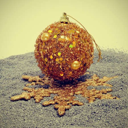 x mas: golden christmas ornaments on a gray grained surface, with a retro effect Stock Photo
