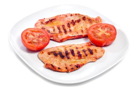 a plate with some slices of barbecued spiced chicken meat and raw tomato on white background Stock Photo - 16262694