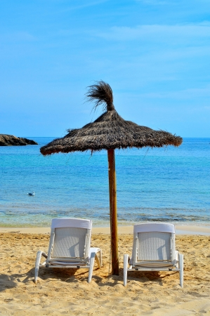 pujols: view of a tropical beach with some straw umbrellas in Formentera, Balearic Islands, Spain