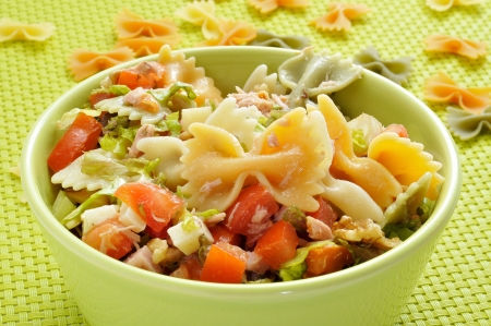 closeup of a bowl with refreshing pasta salad on a draped table with a green tablecloth photo