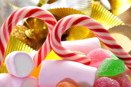 closeup of a pile of candies such as candy canes or marshmallows and some christmas ornaments photo