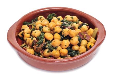 spanisch espinacas con garbanzos, Spinat mit Kichererbsen, als Tapas auf einem weißen Hintergrund serviert