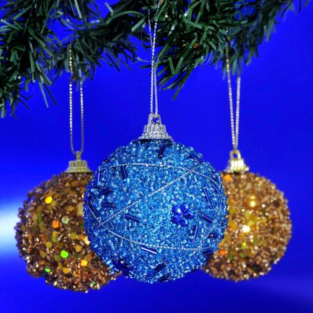 some golden and blue christmas balls hanging of a christmas tree on a blue background photo
