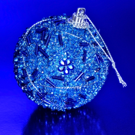 closeup of a blue christmas ball on a blue background photo