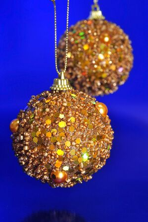 some golden christmas balls hanging of a christmas tree on a blue background photo
