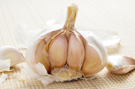closeup of a head of garlics on a beige woven surface Stock Photo - 16487394