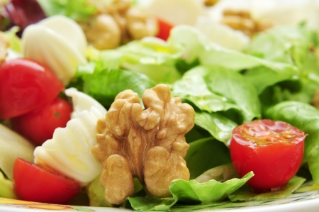 cornsalad: closeup of a plate with salad, with romaine, cherry tomatoes, walnuts and cheese
