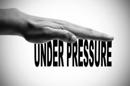 competitividad: una mano del hombre en blanco y negro pulsando la sentencia bajo presi�n escrito en negro