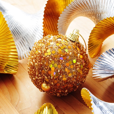 a golden christmas ball and golden and silver garland on a wooden surface photo