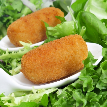 croquettes: closeup of some spanish croquettes in a bed of lettuce served as tapas Stock Photo