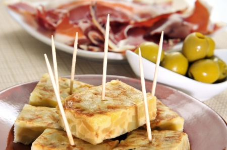 an omelette: some spanish tapas, such as tortilla de patatas, serrano ham and olives