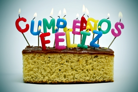feliz: letter-shaped candles of different colors forming sentence cumpleanos feliz, happy birthday in spanish, on a cake