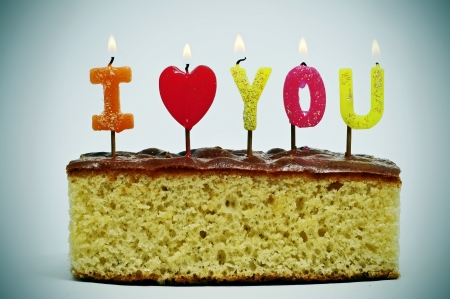 anniversary wishes: letter-shaped candles of different colors forming sentence I love you on a cake