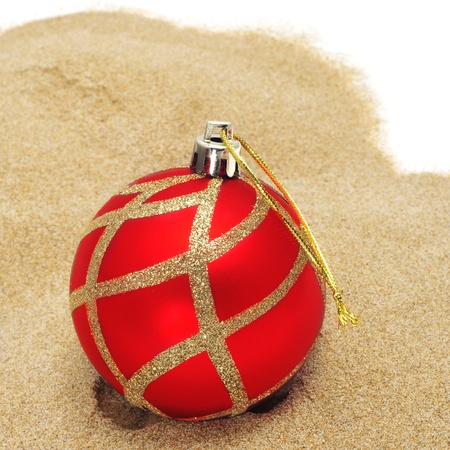 a red christmas ball on the sand, to symbolize christmas time in southern hemisphere photo