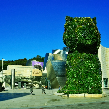 topiary: Bilbao, Spain - November 13, 2012: Guggenheim Museum and Puppy sculpture in Bilbao, Spain. The museum was designed by Frank Ghery and the topiary sculpture, a giant puppy, by Jeff Koons