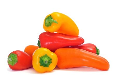 peperoni morso di diversi colori, arancio, rosso e giallo, su uno sfondo bianco