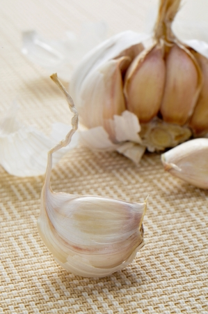 woven surface: Primer plano de una cabeza de ajos en una superficie tejida de color beige
