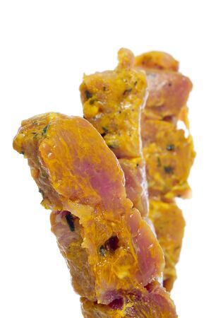 some raw marinated chicken skewers on a white background Foto de archivo