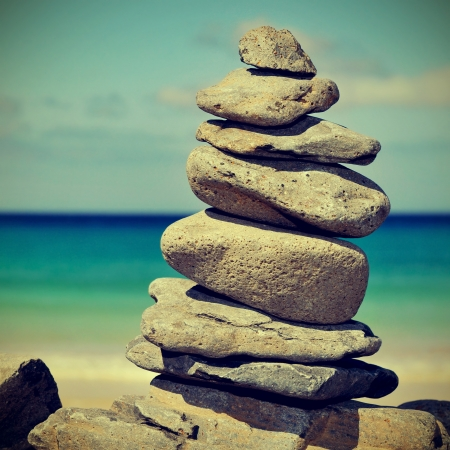closeup of a stack of stones on a beach, with a retro effect photo