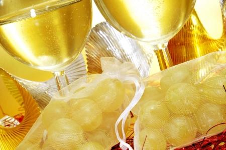 sachets: algunas copas con cava y sobres espa�oles con las doce uvas de la suerte, tradicionales en el A�o Nuevo Foto de archivo