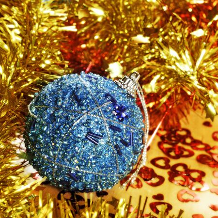 closeup of a shiny blue christmas balls and golden and orange tinsel photo