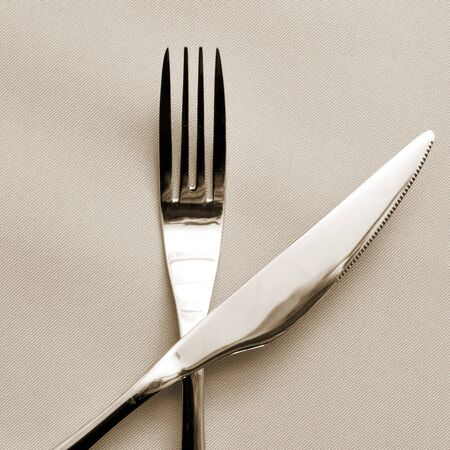 closeup of a knife and a fork on a beige tablecloth photo