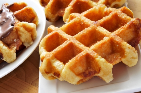 some plates with waffles on a wooden table photo