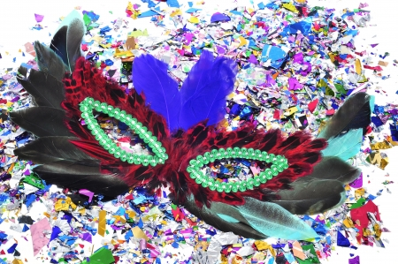 feathers carnival mask and confetti of different colors photo