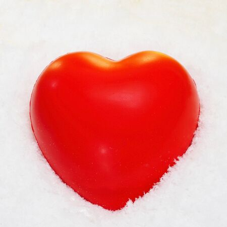 closeup a red heart on the snow photo