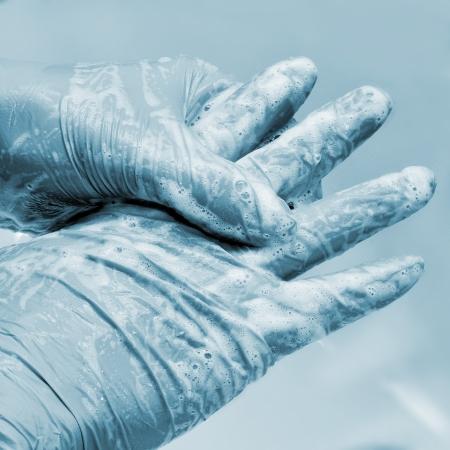 lavandose las manos: alguien con guantes quirúrgicos lavado las manos