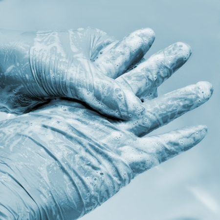 washing hand: someone wearing surgical gloves washing his or her hands Stock Photo
