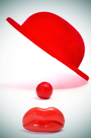 red bowler hat, clown nose and mouth on a white background photo