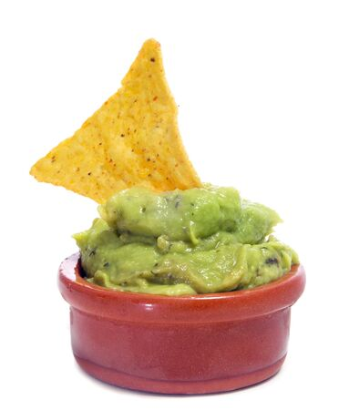 guacamole: a bowl with guacamole and a nacho on a white background