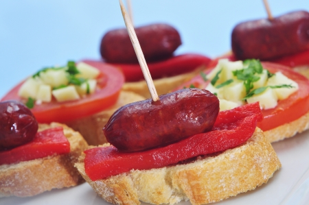 closeup of a plate with spanish pinchos, typical northern sandwiches, some of them made with chorizos an piquillo peppers photo