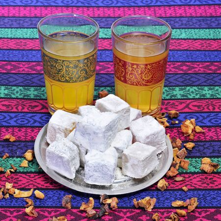 thirstiness: closeup of some ornamented glasses with tea and a plate with some turkish delight