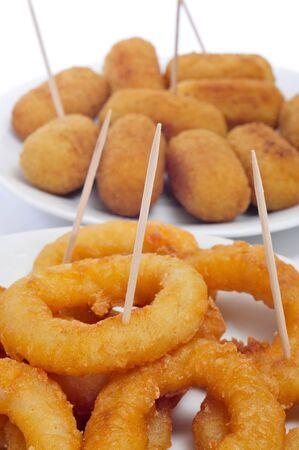 croquettes: closeup of some plates with spanish croquettes and calamares a la romana, squid rings, served as tapas Stock Photo