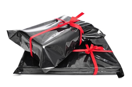 a pile of gifts wrapped with black plastic and tied with red ribbons on a white background  photo