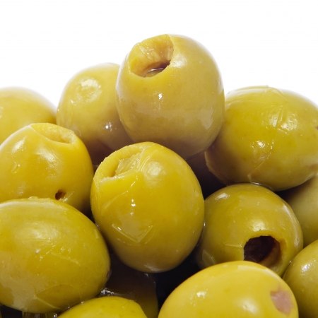 pitted: closeup of a pile of spanish olives tapas on a white background