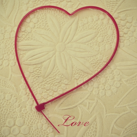 zip tie: word love and a heart-shaped zip tie on a flower patterned background Stock Photo