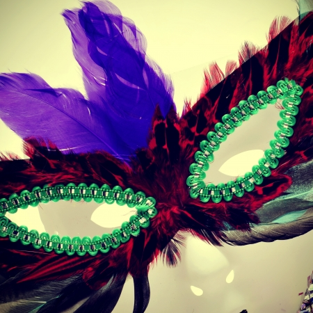 carnivale: closeup and cutout of a carnival mask with feathers of different colors