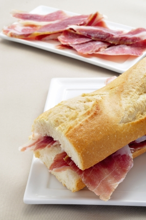 embutido: closeup of a spanish serrano ham sandwich in a plate