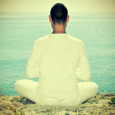 buddhist meditation: someone meditating in front of the sea