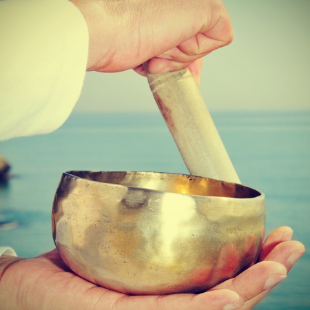 terapias alternativas: alguien tocando un cuenco tibetano frente al mar