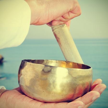musicoterapia: qualcuno giocare una ciotola tibetano di fronte al mare