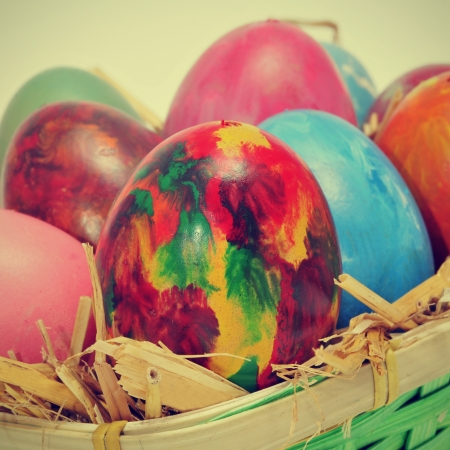 some easter eggs of different colors on a basket with straw, with a retro effect photo